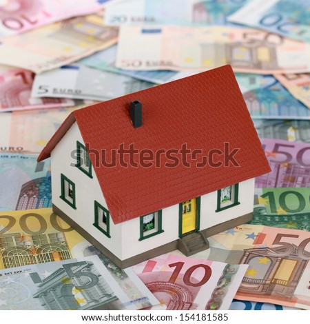 Symbolic picture financing a real estate with a house on banknotes - stock photo