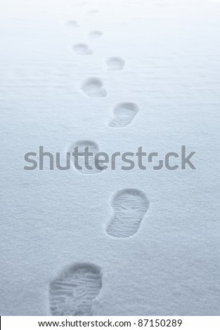 symbolic picture showing boot traces walking away in fresh fallen snow