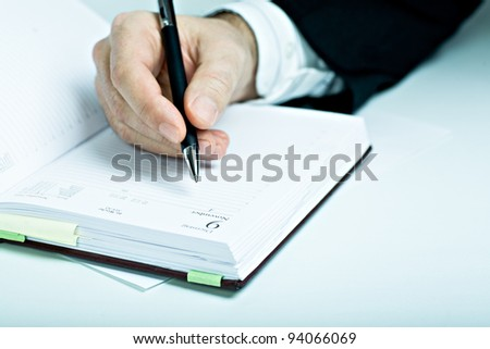 Symbolic picture. Suited man with schedule book. - stock photo