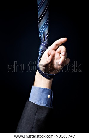 Symbolic picture with mans hand hanging in the noose - stock photo