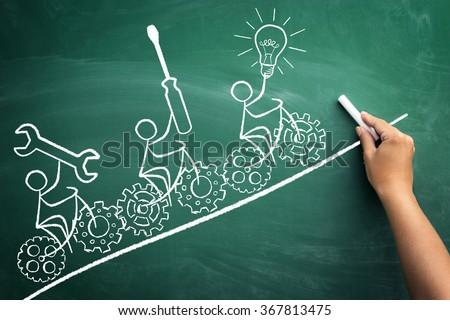symbolic representation of teamwork with a drawn stickmen who ride their bikes on blackboard  - stock photo