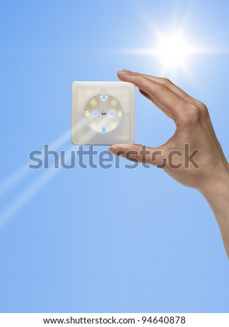 symbolic solar energy theme showing the sun and sky with human hand holding a electrical socket while sunbeams falling through - stock photo