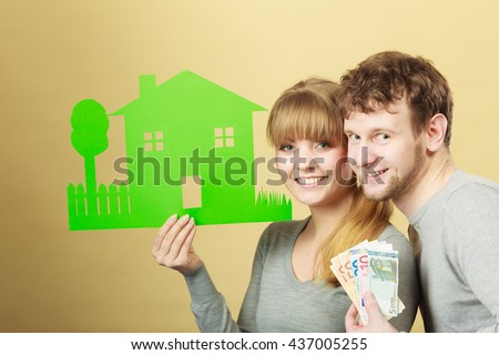 Symbolism property ownership finances mortgage savings concept. Wife and husband holding items. Young couple shows cash with house cutout. - stock photo