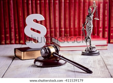 Symbols of law in court library. Judge gavel, wooden paragraph, goddess of justice Themis and legal codes. Law concept - stock photo