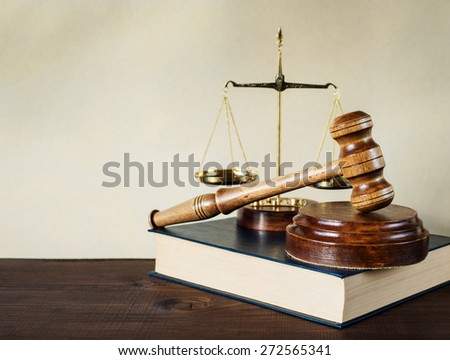 Symbols of law: wood gavel, soundblock, scales and thick old book - stock photo