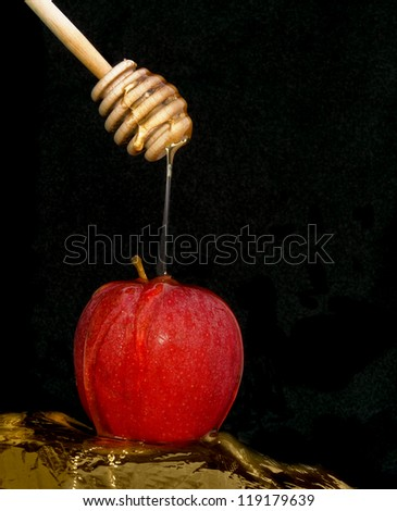 Symbols of the Jewish New Year - sweet honey flowing over a delicious red apple; isolated on a black background. - stock photo