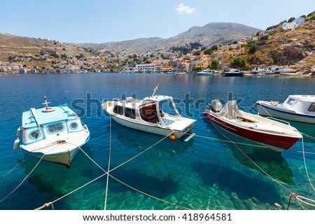 SYMI, GREECE - JUNE 12,2015: Fishing boats moored in Yialos harbour on June 12, 2015 on Symi island, Greece. Symi is easy and most popular destination for day tripping from Rhodes island. - stock photo