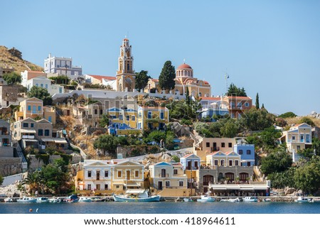 SYMI, GREECE - JUNE 12,2015: View of a coastline street and fishing boats moored in Yialos harbour on Symi island,Greece. Symi is easy and most popular destination for day tripping from Rhodes island. - stock photo