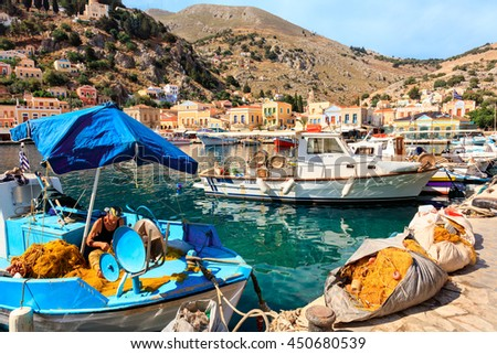 SYMI ISLAND, GREECE - JUNE 11, 2016: Fisherman repairing nets in picturesque harbor on the island of Symi in Agean Sea. - stock photo