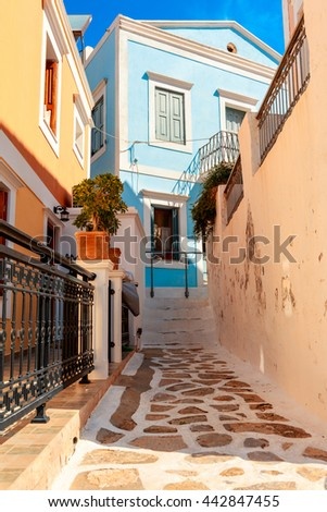 SYMI ISLAND, GREECE - JUNE 11, 2016: Narrow cobbled street with neo-classical houses on the Greek island of Symi. - stock photo