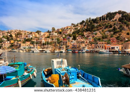SYMI ISLAND, GREECE - JUNE 11, 2016: Neo-Classical houses and fishing boats in picturesque harbor on the island of Symi in Agean Sea. - stock photo