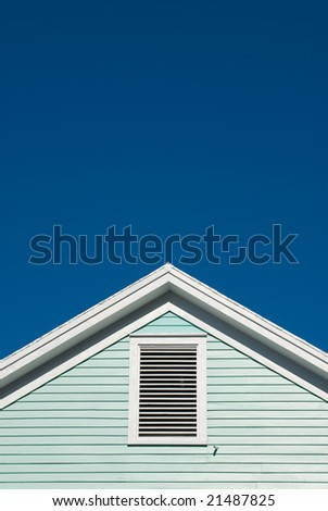 Symmetric detail shot of roof gable showing ventilation panel - stock photo