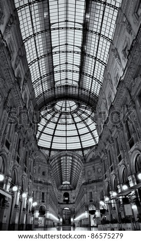 Symmetrical black and white night shot of the hall of the landmark arcade or covered mall, Galleria Vittorio Emanuele II in Milan, Italy - stock photo