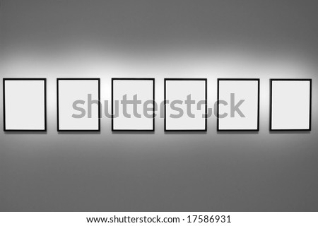 Symmetrical series of six empty picture frames hanging on a gallery wall - stock photo