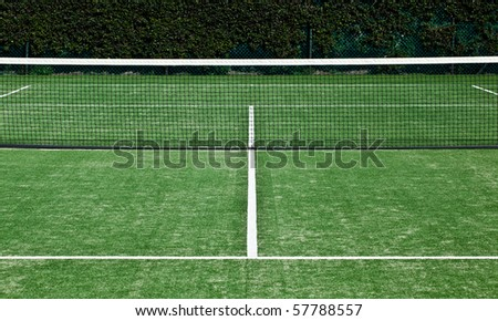 Symmetrical shot of tennis net and forecourt.