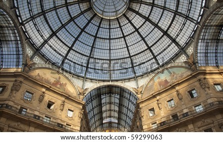 Symmetrical shot of the famous luxury shopping mall Galleria Vittorio Emanuele II in Milan, Italy, showing the spectacular ceiling of this gate to luxury - stock photo