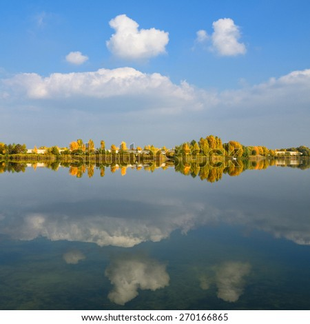Symmetrical view of autumn trees reflected in the lake with blue sky and colorful trees - stock photo