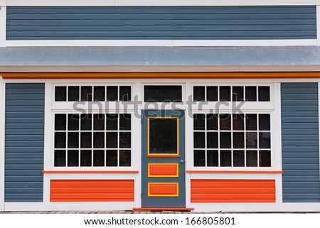 Symmetrical view of the front door and entrance to a quaint colorful wooden house with large cottage pane windows on either side - stock photo