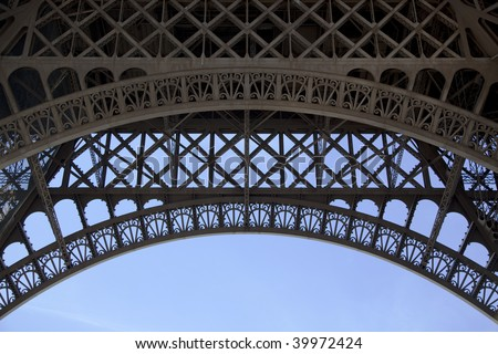 Symmetrical view of the steel structure under the Eiffel Tower in Paris - stock photo