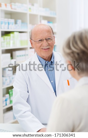 Sympathetic friendly male pharmacist standing at the counter in the pharmacy talking to a female patient listening to her problems with a gentle smile - stock photo