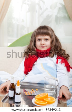 Sympathetic little sick girl in red scarf under blanket in bed is taking a salver with pills, sprays and orange - stock photo