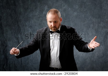 Symphony conductor directing wit a baton. - stock photo