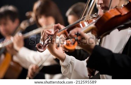 Symphony orchestra first violin section performing on dark background. - stock photo