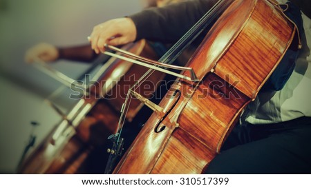 Symphony orchestra on stage, hands playing violin. Shallow depth of field, vintage style.