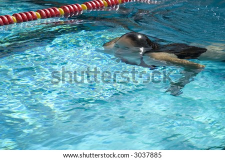 Synchronized swimmer in the water (sun shining on her hair)