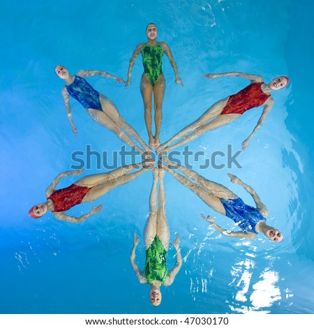 Synchronized swimmers hold pose for camera - stock photo
