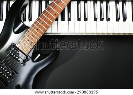 Synthesizer and electric guitar on dark background
