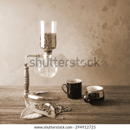 Syphon coffee preparing in the morning light and waiting two cups with bean and leaves vintage color shade - stock photo