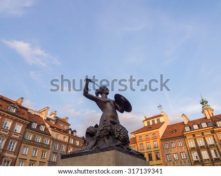 Syrenka (mermaid) sculpture on Warsaw's Old Town Market Place on a late summer afternoon. Wide angle, horizontal orientation. - stock photo