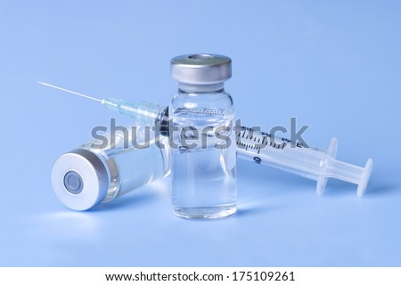 Syringe and vials of injectable medication on blue.