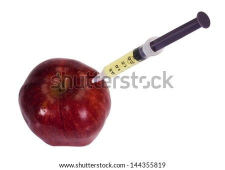 Syringe being injected into an apple - stock photo