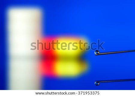 Syringe needle with a vaccine drop close up, against a tablet and a pill not in focus. - stock photo