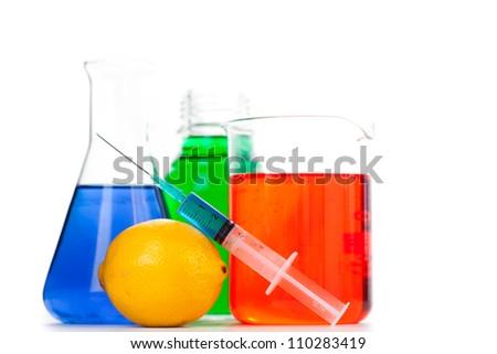 Syringe putting on an orange next to beakers against a white background - stock photo