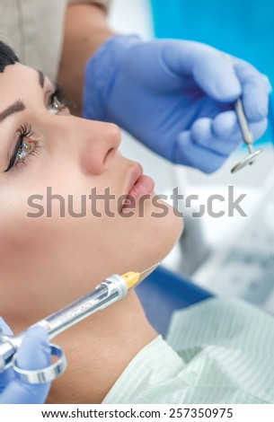 Syringe with anesthetic near the cheeks client dentist. Dentist makes the process of treatment of a beautiful young girl.