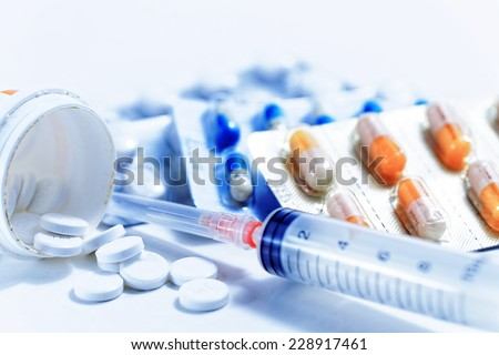 Syringe with glass vials and medications pills drug - stock photo
