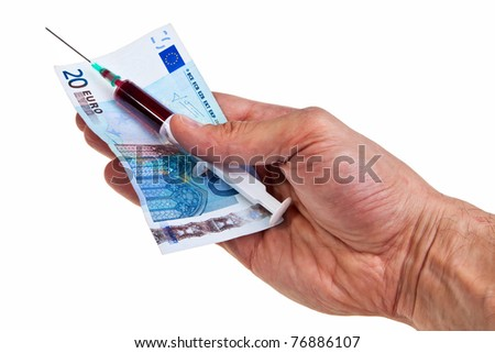 Syringe with red liquid and 20 Euro banknote hold by caucasian male hand over white background.