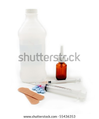 Syringes bandages, rubbing alchohol and pills against a white background