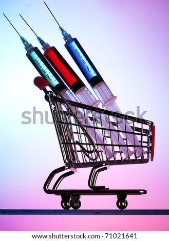 Syringes in a miniature shopping cart - stock photo