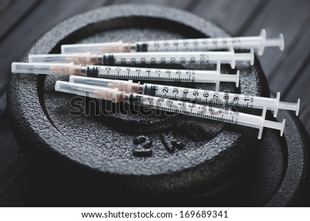 Syringes on dumbbell weight plates, close-up - stock photo
