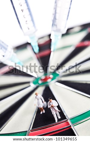 Syringes stuck in a dartboard with medical figures.