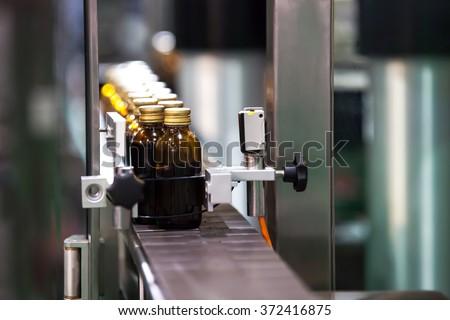 Syrup Bottles transfer on Conveyor Belt System - stock photo