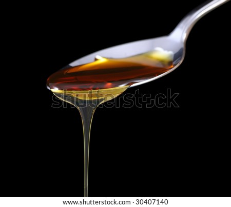 Syrup dripping off a spoon on black background - stock photo