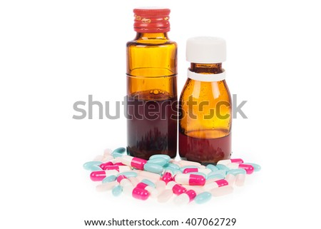 Syrup Medication Bottles and Medicine in Spoons on white background - stock photo