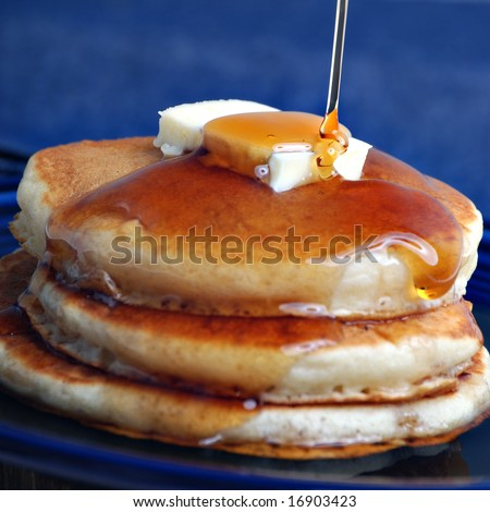 syrup pouring onto pancakes - focus on syrup - stock photo