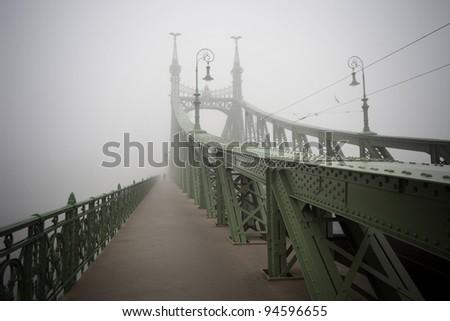 Szabadsag hid, monumental austro hungarian green bridge in fog - stock photo