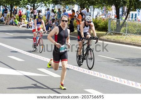 SZCZECIN, POLAND - JULY 06, 2014: Runner and cyclists during first Triathlon Szczecin race. - stock photo